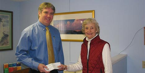 Peggy Gifford, CFNan Board Chairman, gives Family & Children's Services ED Peter Swenson a grant check.