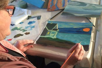 Woman Painting a picture of a house by the water.