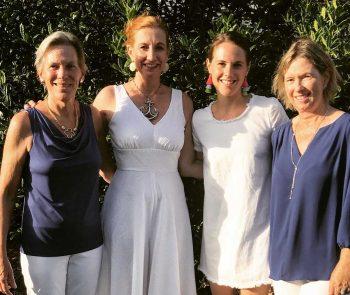 Four women in business causal dress.