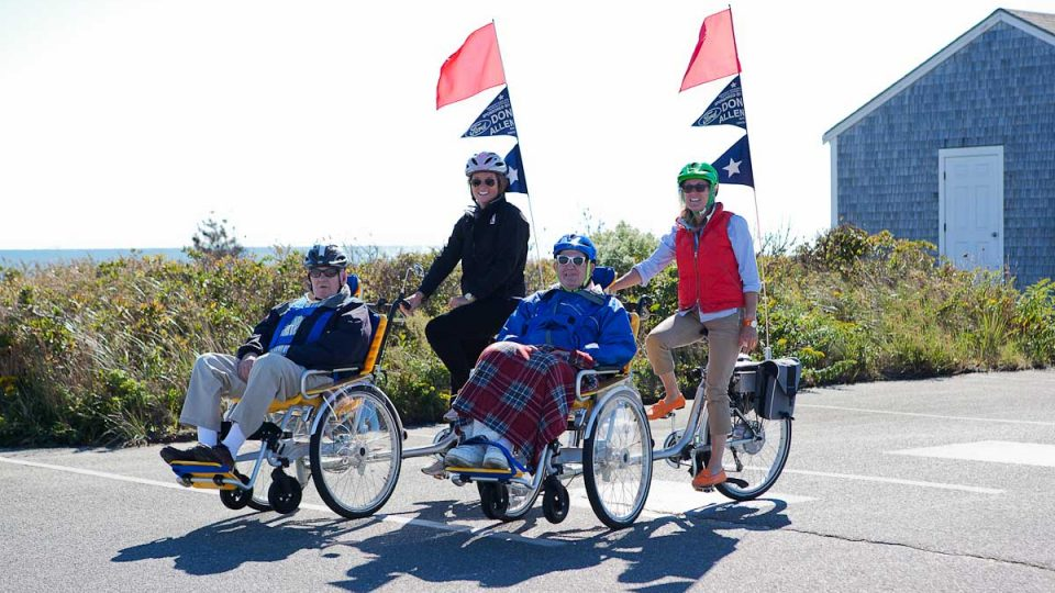 Four adults using wheelchair bikes.