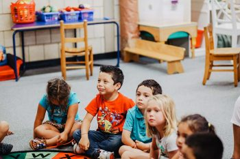 Young children seatin on the floor in a classroom.