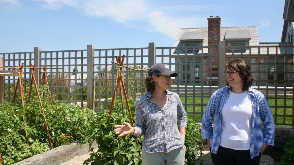Two women standing in a garden.