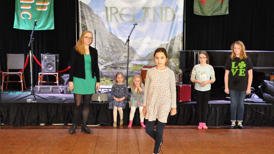 Girls dancing in front of Ireland banner.